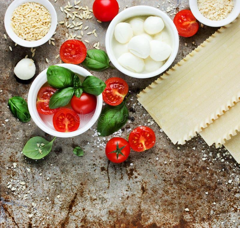 Ingredientes para lasanhas: manjericão fresca, tomates de cereja, mozz do bebê fotos de stock royalty free