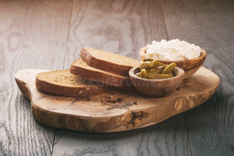 Ingredientes para los bocadillos con pan de centeno, queso cremoso y pepinos adobados foto de archivo