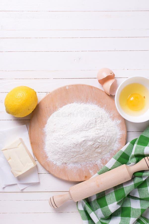 Ingredientes para a massa - farinha, ovo, manteiga, limão no woode branco foto de stock