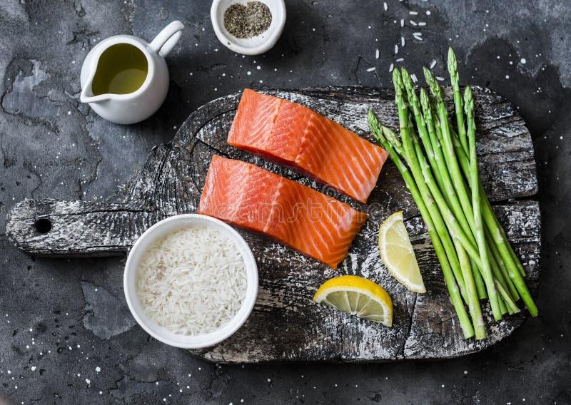 Ingredientes para o almoço - salmão orgânico cru fresco, aspargo verde e arroz em um fundo escuro, vista superior imagem de stock royalty free