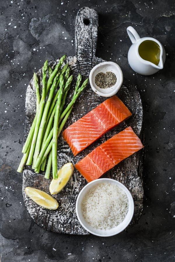 Ingredientes para o almo?o - salm?o org?nico cru fresco, aspargo verde e arroz em um fundo escuro, vista superior imagem de stock