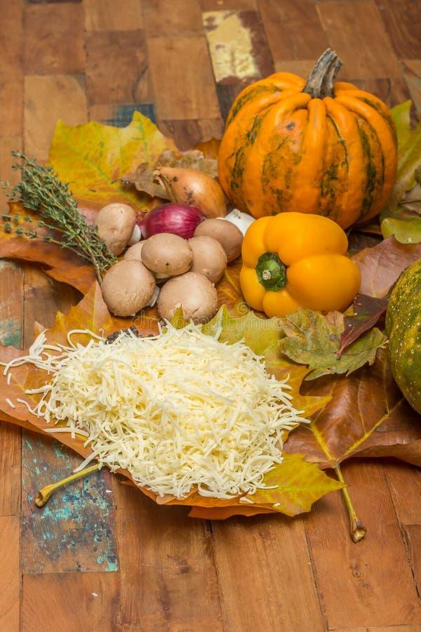 Ingredientes para o fondue de queijo nas folhas de outono fotografia de stock royalty free