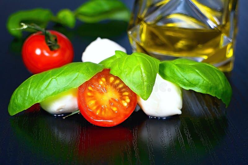 Ingredientes para a preparação da salada mediterrânea de Caprese: tomates, mussarela, folhas da manjericão e azeite fotografia de stock