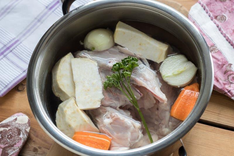 Ingredientes para preparar o caldo do osso da galinha em um potenciômetro foto de stock