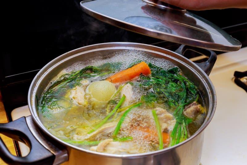 Ingredientes para preparar o caldo em uma galinha do potenciômetro, cebolas do osso da galinha, raiz de aipo, cenouras, salsa imagens de stock