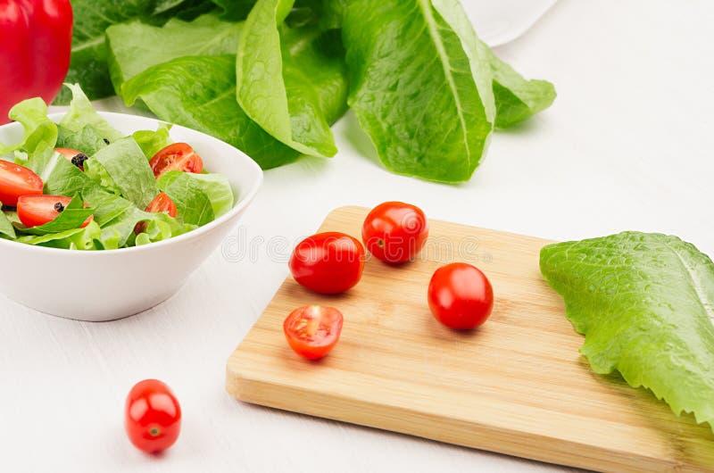 Ingredientes para a salada saudável da mola do vegetariano - verdes frescos, tomates, pimenta no cuttingboard no fundo de madeira fotografia de stock