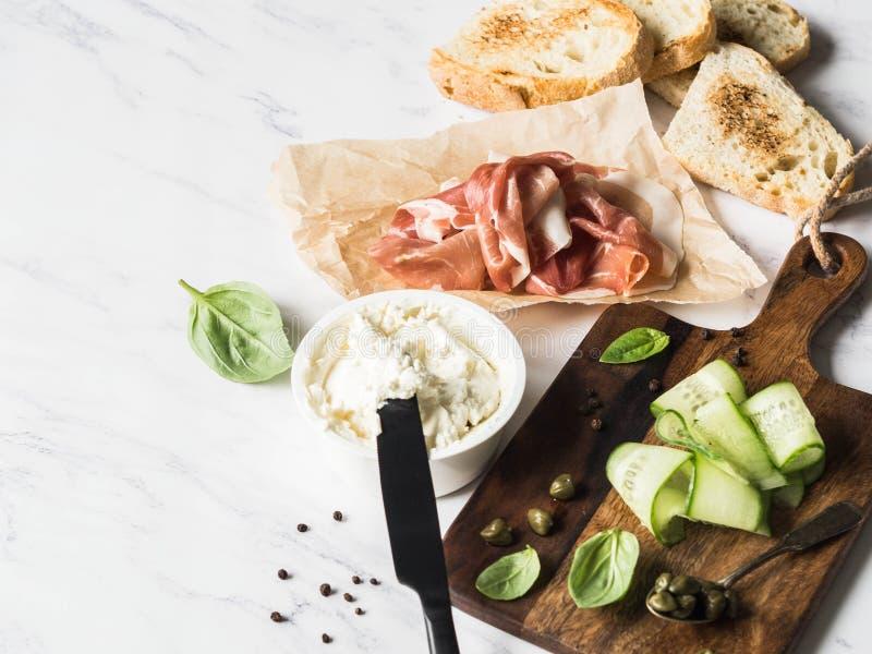 Ingredientes para sanduíches da preparação com queijo creme, prosciutto, fatias do pepino, alcaparras, manjericão em brindes grel foto de stock royalty free