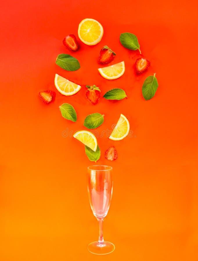 Ingredientes planos de la limonada de la fresa de la endecha - rebanadas del limón, hojas de menta y fresas cayendo en un vidrio  foto de archivo libre de regalías