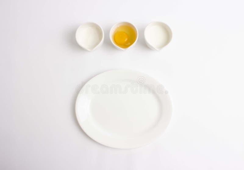 Ingredientes que cuecen en el fondo blanco foto de archivo