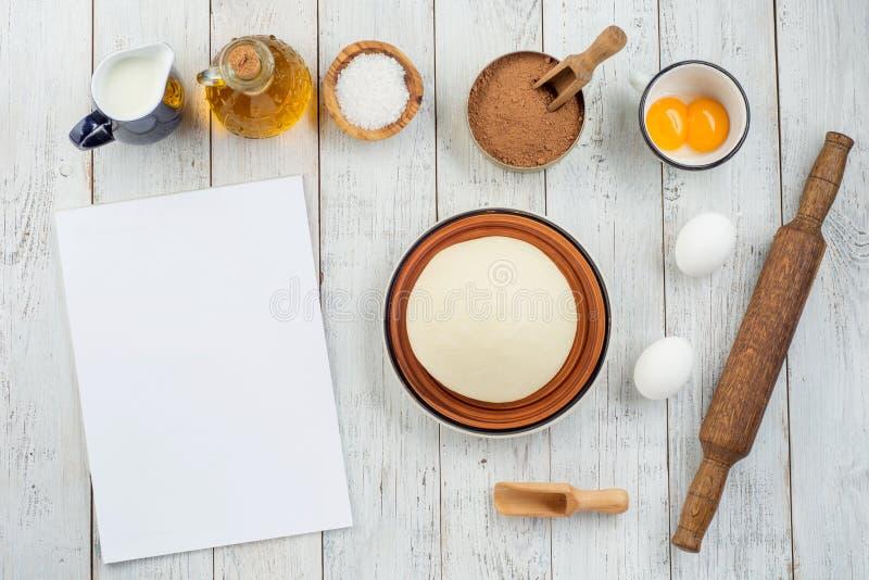Ingredientes que cuecen sanos - harina, aceite de oliva, huevos, leche, sal, yemas de huevo, cacao, pasta sobre un fondo blanco d imagen de archivo