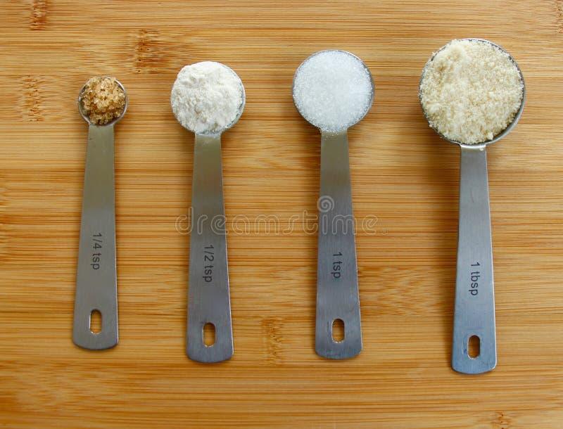 Ingredientes que cuecen y cucharas dosificadoras imagenes de archivo