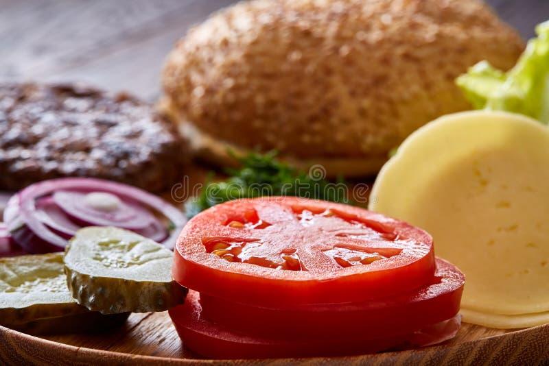 Ingredientes saborosos do Hamburger organizados artisticamente na placa de madeira, close-up, vista superior, foco seletivo foto de stock royalty free