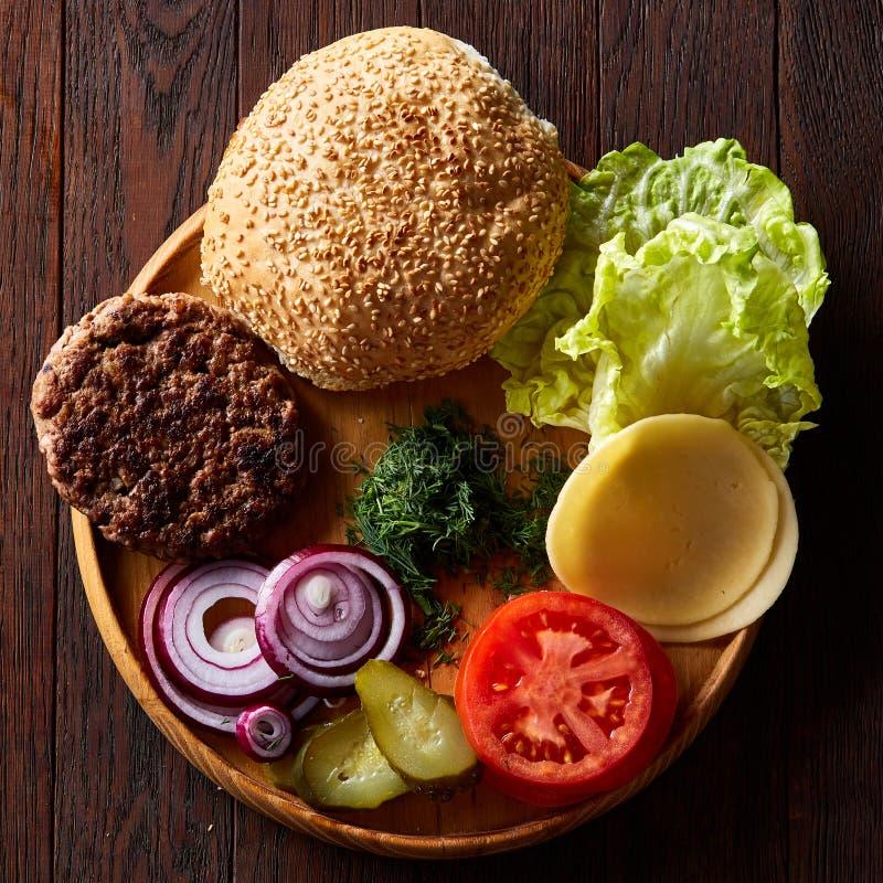Ingredientes saborosos do Hamburger organizados artisticamente na placa de madeira, close-up, vista superior, foco seletivo fotos de stock