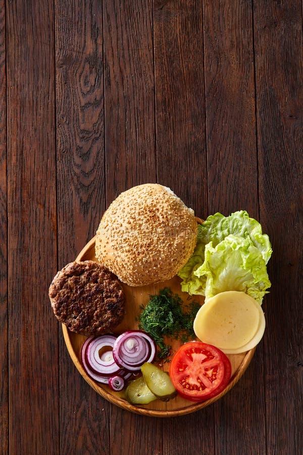 Ingredientes saborosos do Hamburger organizados artisticamente na placa de madeira, close-up, vista superior, foco seletivo imagem de stock royalty free