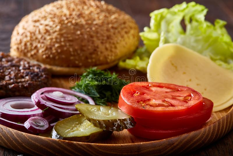 Ingredientes saborosos do Hamburger organizados artisticamente na placa de madeira, close-up, vista superior, foco seletivo imagens de stock royalty free