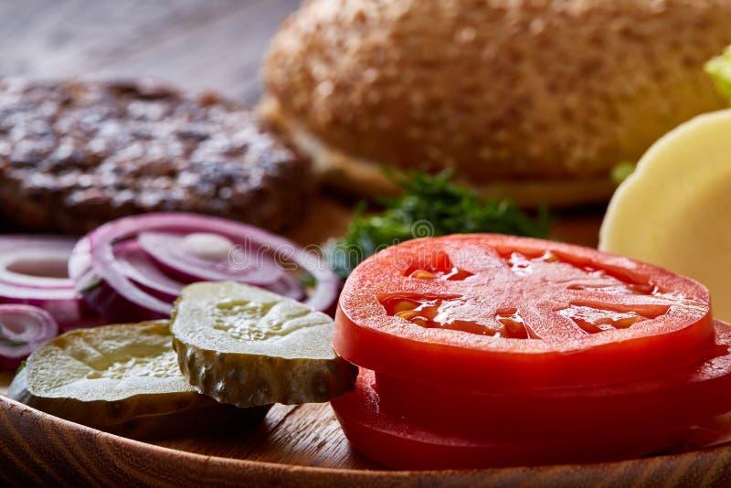 Ingredientes saborosos do Hamburger organizados artisticamente na placa de madeira, close-up, vista superior, foco seletivo fotografia de stock royalty free