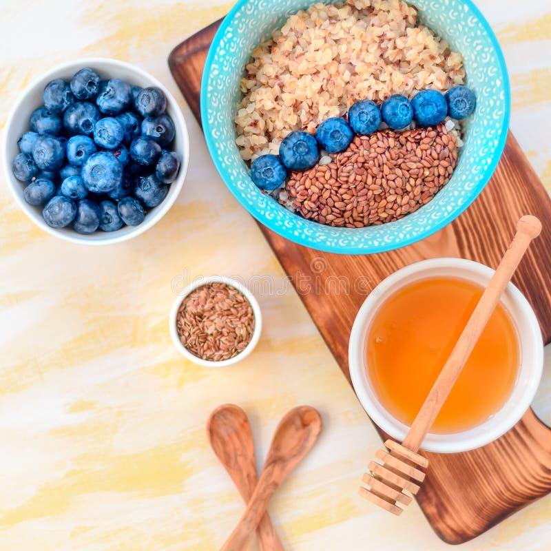 Ingredientes sanos del desayuno Los arándanos del alforfón acuñan la miel en el fondo de madera blanco, visión superior, espacio  imagenes de archivo