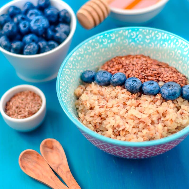 Ingredientes sanos del desayuno Los arándanos del alforfón acuñan la miel en el fondo de madera blanco, visión superior, espacio  imagen de archivo libre de regalías