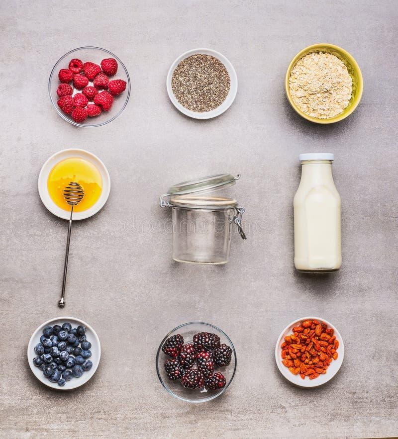 Ingredientes sanos del desayuno: miel, harina de avena, semillas de Chia, bayas de Goji, bayas frescas y botella de leche con el  fotografía de archivo