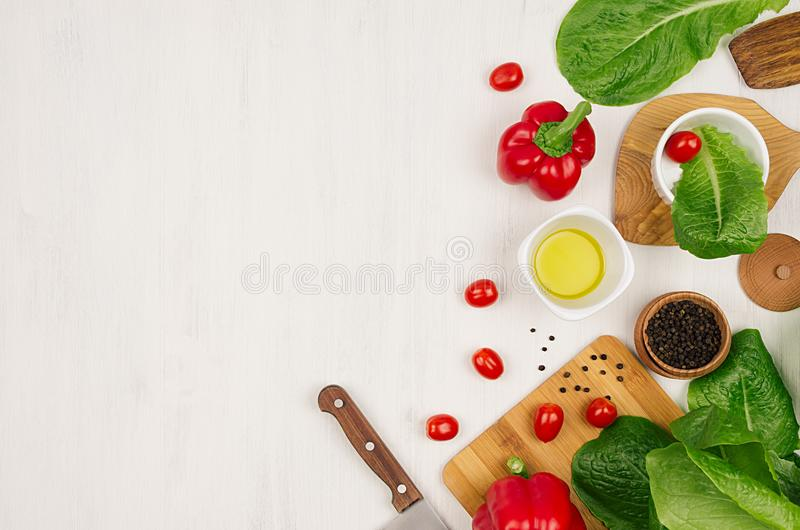 Ingredientes saudáveis do vegetariano para a salada verde e o kitchenware frescos da mola na placa de madeira branca, vista super imagens de stock royalty free