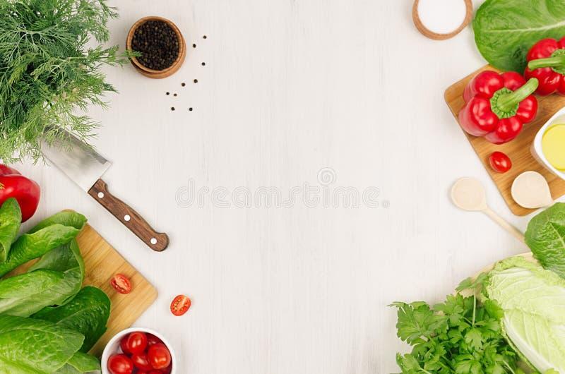 Ingredientes saudáveis do vegetariano para a salada verde e o kitchenware frescos da mola na placa de madeira branca, vista super imagem de stock royalty free