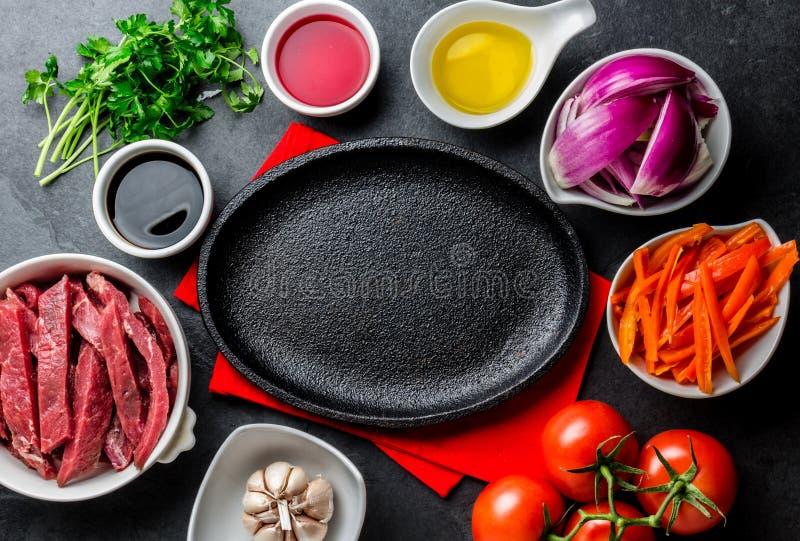 Ingredientes voor het koken Peruviaanse saltado van schotellomo - haasbiefstukrundvlees, groenten rond zwarte plaat Peutermening stock afbeelding