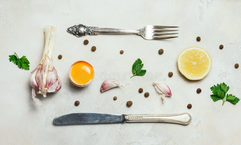 Ingredientes y cubiertos orgánicos de la comida: huevo, ajo y perejil en el fondo concreto rústico blanco Visión superior, endech imagen de archivo libre de regalías