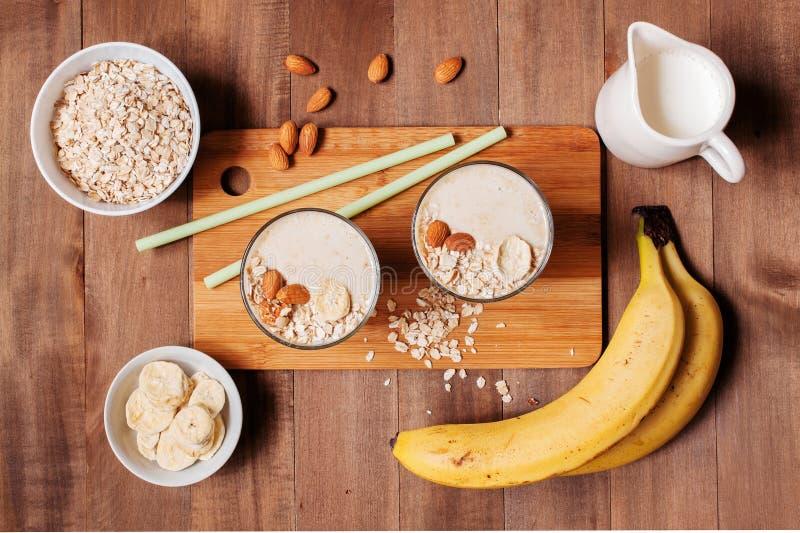 Ingredientes y dos porciones de smoothies en la tabla de madera fotografía de archivo