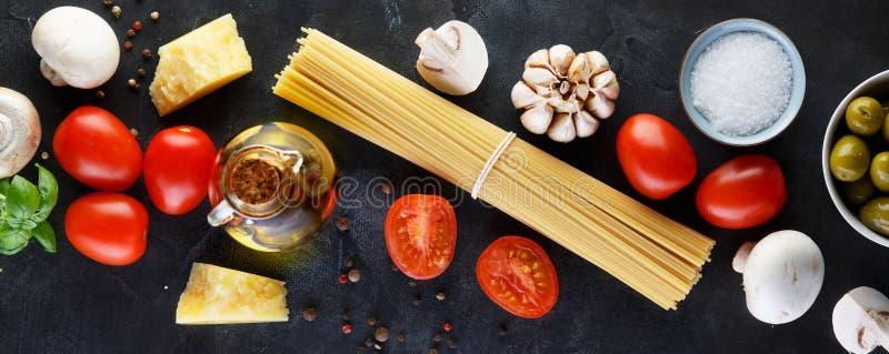Ingredienti alimentari per pasta italiana, spaghetti sul fondo di pietra nero dell'ardesia bandiera immagine stock libera da diritti