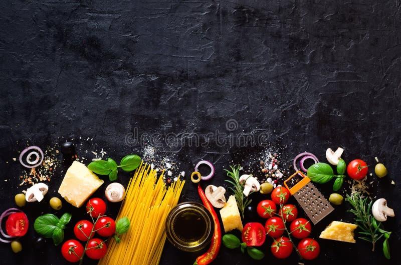 Ingredienti alimentari per pasta italiana, spaghetti sul fondo di pietra nero dell'ardesia copi lo spazio del vostro testo immagine stock libera da diritti