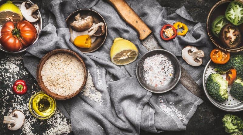 Ingredienti alimentari vegetariani sani con il limone, il riso e le verdure su fondo rustico scuro fotografia stock