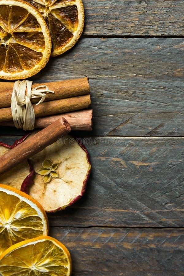 Ingredienti caldi dell'aroma della bevanda di vacanza invernale La mela arancio secca affetta i bastoni di cannella sul vecchio l fotografie stock