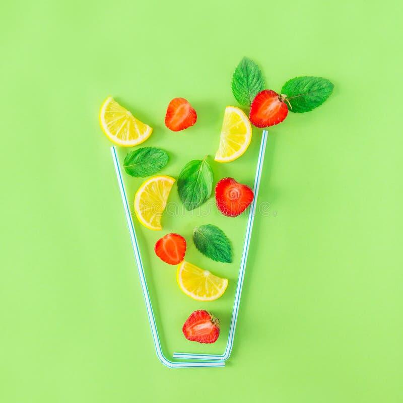 Ingredienti creativi della limonata della fragola della disposizione - limone, menta, bacche che cadono in vetro fatto con le pag fotografie stock libere da diritti