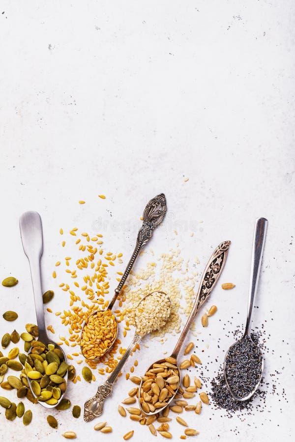 Ingredienti culinari: semi della zucca, di un lino, di un sesamo, del girasole e del papavero in cucchiai del metallo su una tavo fotografia stock