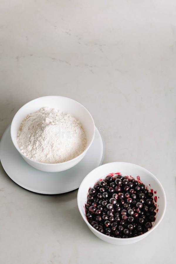 Ingredienti del ribes nero e della farina per cuocere Vista superiore, primo piano Ribes nero e zucchero in ciotole nel bianco immagini stock