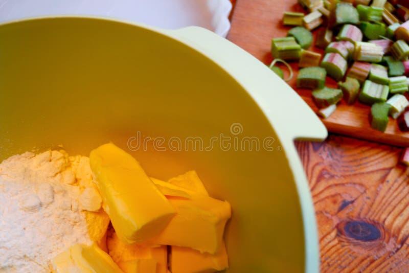 Ingredienti della crosta di torta in una ciotola Rabarbaro tagliato nei precedenti closeup immagini stock