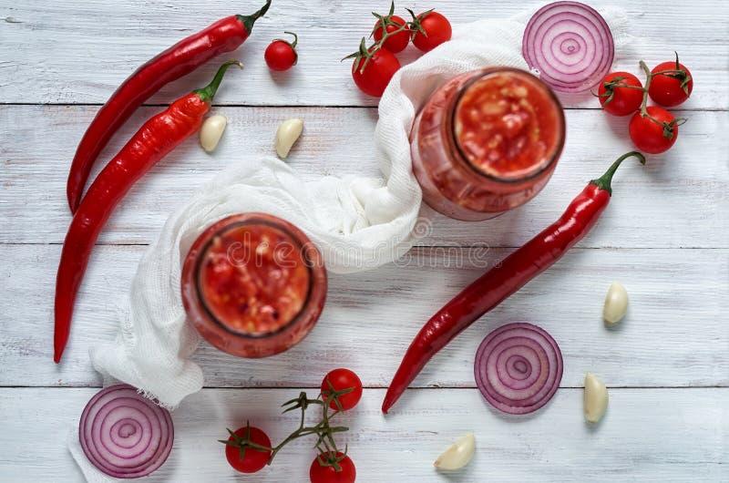 Ingredienti della minestra di zuppa di verdure fredda - tre peperoncini rossi caldi, anelli di cipolla, aglio e piccoli pomodori  fotografia stock libera da diritti