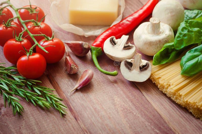 Ingredienti della pasta Ingredienti per la cottura della pasta italiana - spaghetti, pomodori, basilico, petrolio ed aglio Alimen immagine stock