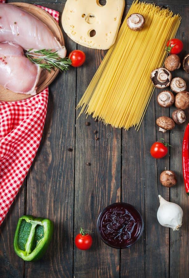 Ingredienti della pasta Pomodori ciliegia, pasta degli spaghetti, raccordo del pollo e funghi sulla tavola di legno immagini stock