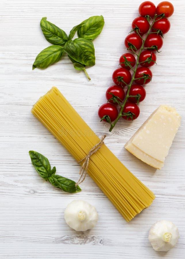 Ingredienti della pasta: spaghetti, parmigiano del formaggio, aglio e pomodori con basilico su superficie di legno bianca, vista  fotografie stock