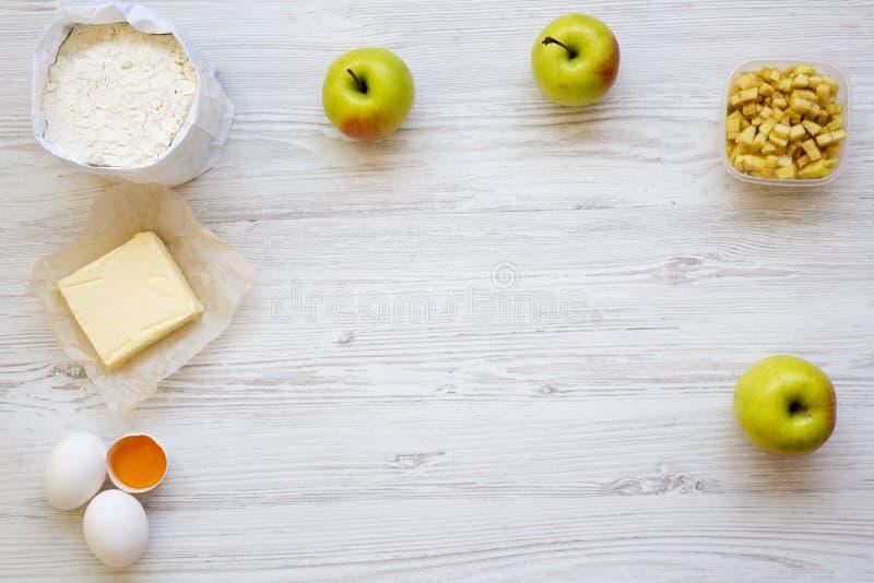 Ingredienti della torta di mele o dello strudel di ricetta della preparazione su fondo di legno bianco, vista superiore Disposizi fotografie stock libere da diritti