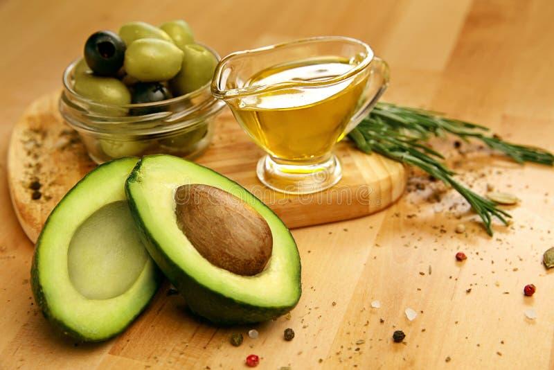 Ingredienti di alimento Avocado di Olive Oil With Olives And sulla Tabella immagine stock libera da diritti