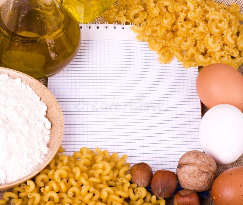 Ingredienti di alimento saporiti e penne italiano della pasta immagine stock