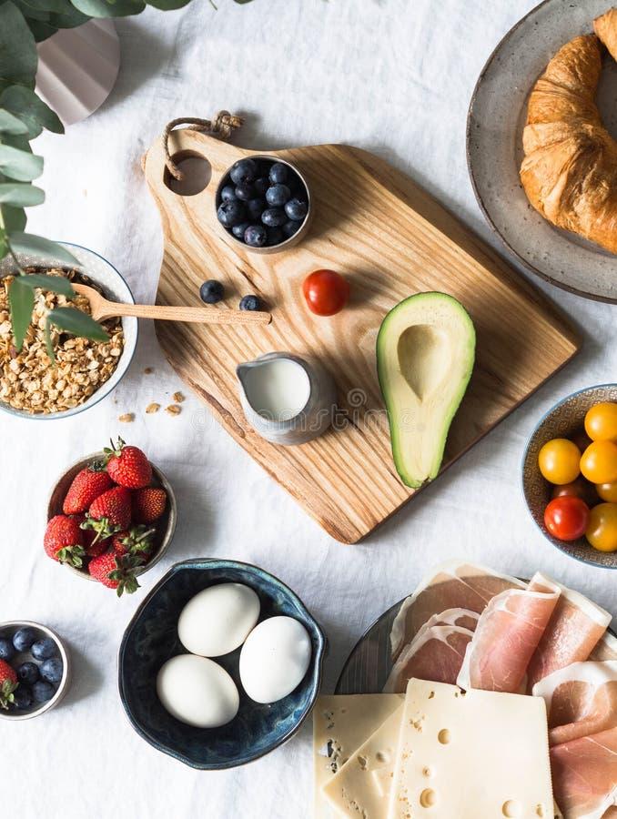 Ingredienti differenti per un formaggio vario della prima colazione, prosciutto di Parma, pomodori ciliegia, avocado, uova, grano fotografia stock