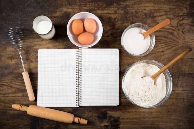 Ingredienti e libro di cucina di cottura sulla tavola immagine stock libera da diritti