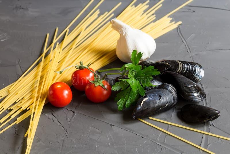Ingredienti freschi per la cottura della pasta dei frutti di mare - composizione degli spaghetti, delle cozze, del pomodoro, dell fotografia stock