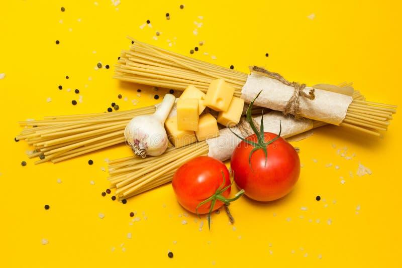 Ingredienti italiani della pasta su un fondo giallo, vista superiore fotografia stock
