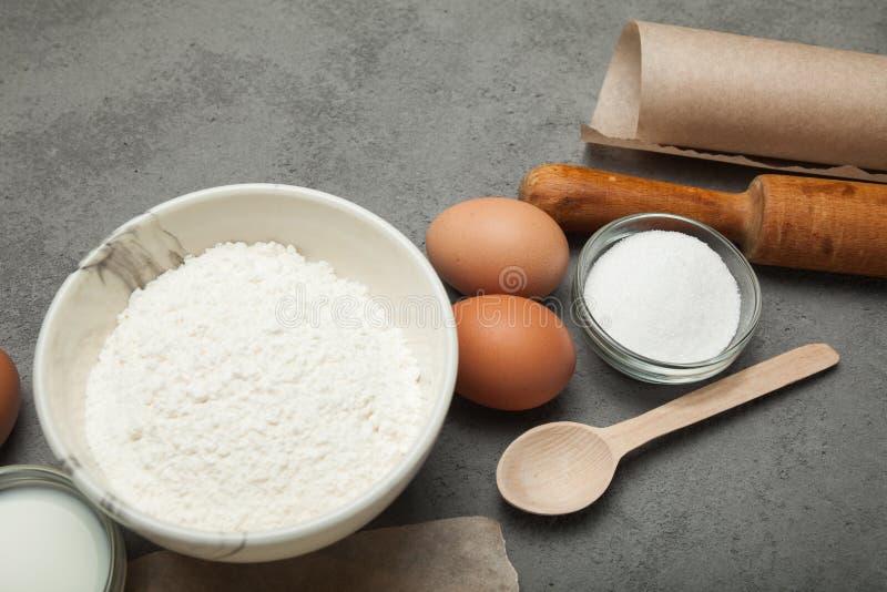 Ingredienti naturali per cuocere - uova, farina, zucchero, latte, burro con gli utensili di legno della cucina su un fondo grigio immagini stock libere da diritti