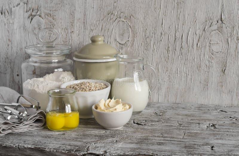 Ingredienti per cuocere - farina, latte, burro, uova su una tavola di legno leggera Spazio libero per testo fotografia stock