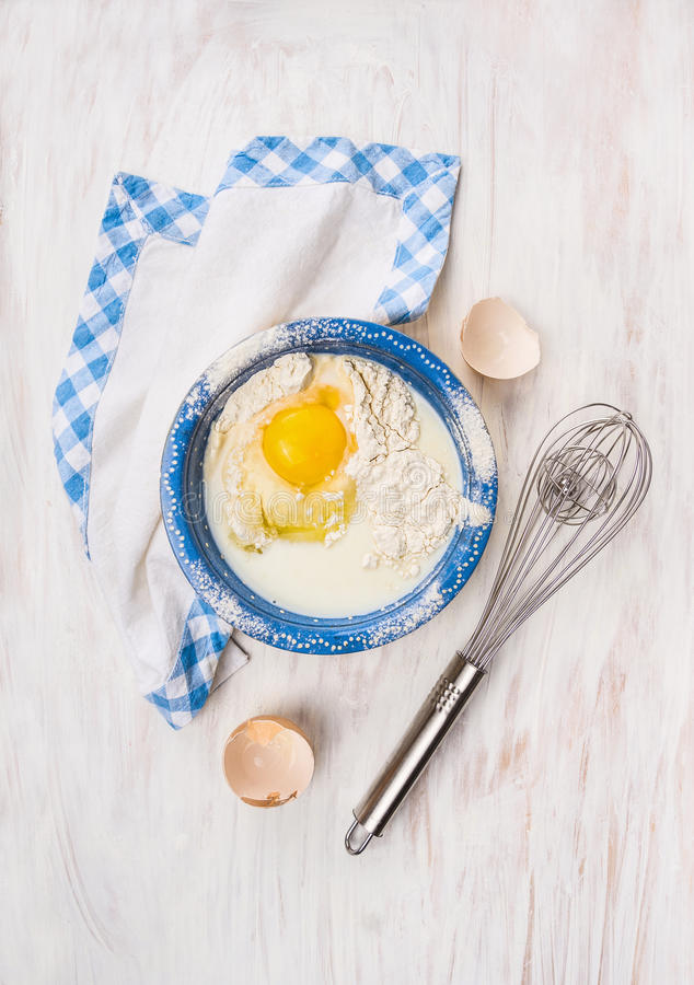 ingredienti per cuocere: farina, uovo, latte in ciotola blu fotografia stock libera da diritti